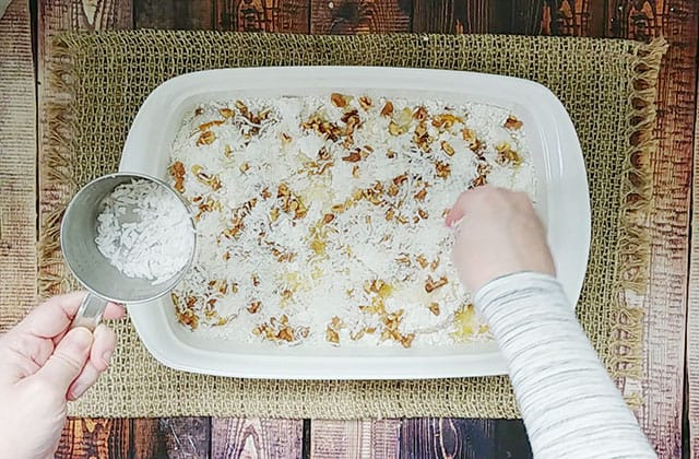 Sprinkling walnuts and coconut over top of cake in a baking dish