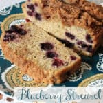 Blueberry zucchini bread sliced on a printed blue plate