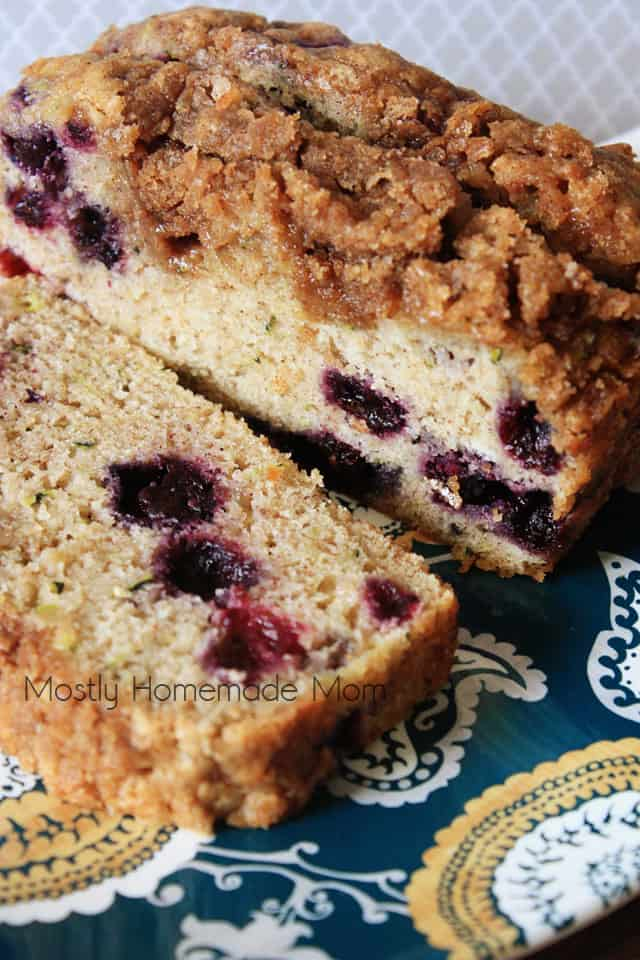A slice of blueberry zucchini bread on a blue plate
