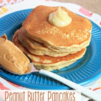 A blue plate with peanut butter pancakes and a spoon of peanut butter