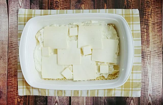 Sliced American cheese and butter over piegrogi casserole