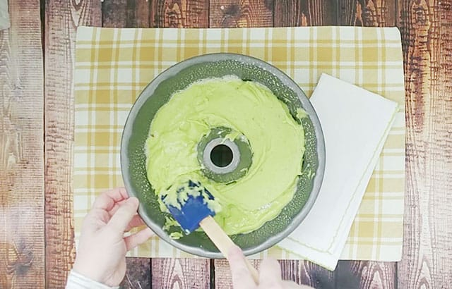 Spreading pistachio cake batter into a bundt pan