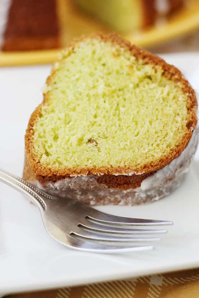 A slice of pistachio cake with glaze on a white plate with a fork
