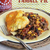 Tamale pie on a plate topped with cornbread and cheese