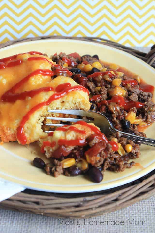 Tamale pie on a plate with cornbread and sriracha