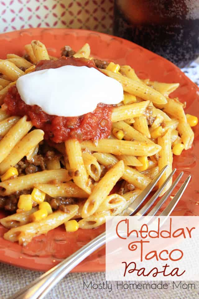 A plate of taco pasta topped with salsa and sour cream with a fork next to it