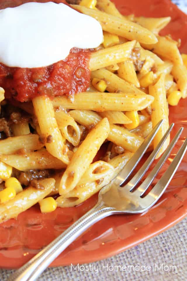 A close up of taco pasta on an orange plate with a fork and sour cream