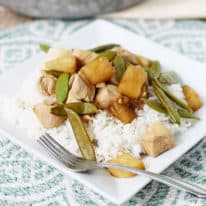Pineapple chicken with sugar snap peas on a square plate with white rice