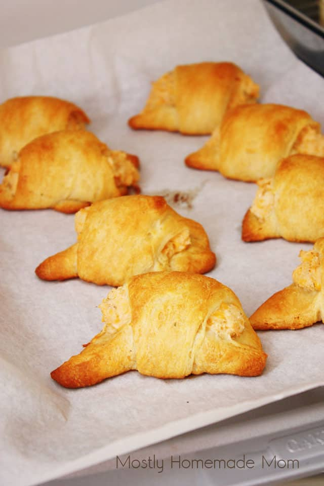Chicken crescent rolls lined up on a cookie sheet after being baked in the oven