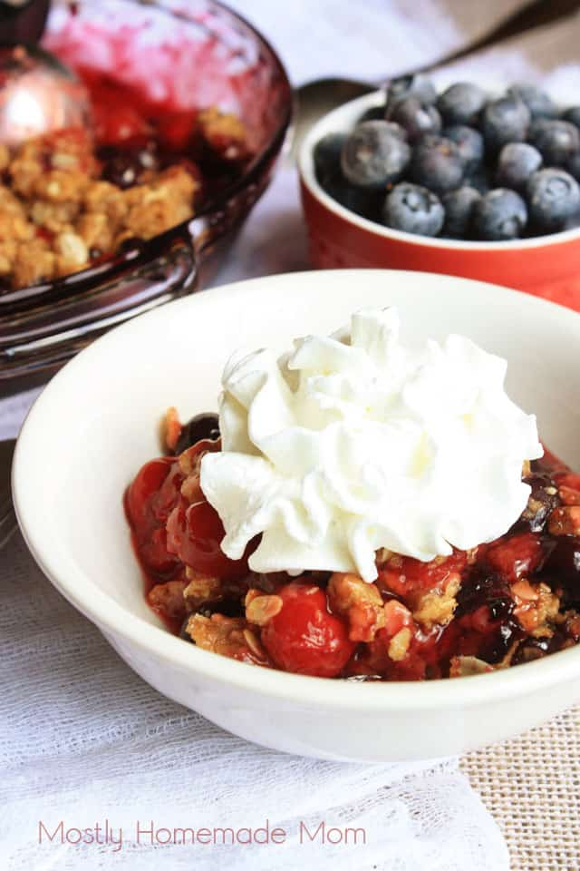 Berry crisp in a white bowl topped with whipped cream