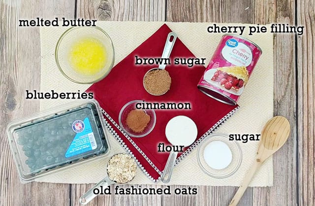 Ingredients to make berry crisp on a yellow placemat