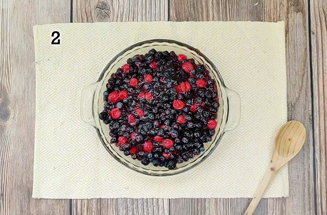 Blueberries and cherry pie filling in a glass pie plate