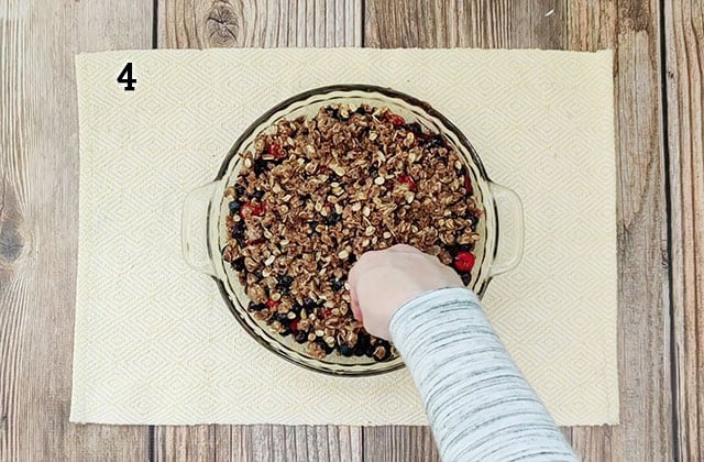 Sprinkling oat topping onto berry crisp in pie plate