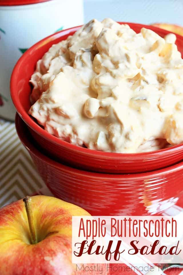 Apple butterscotch fluff salad in a stacked red bowl with an apple in front of it