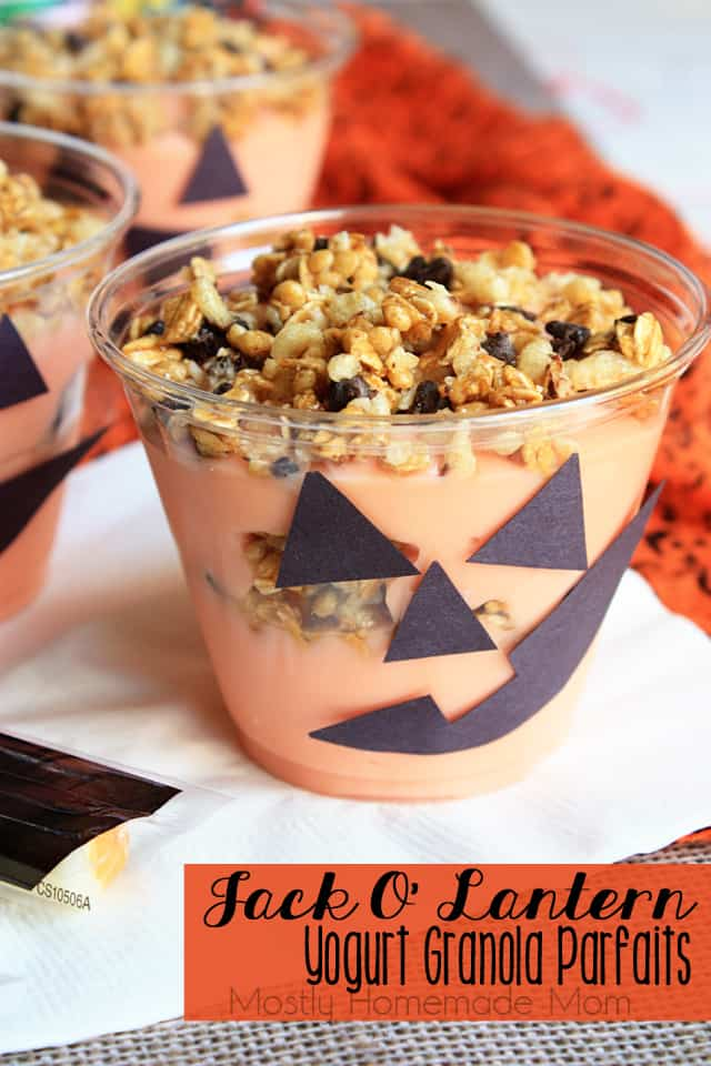 A jack o lantern parfait in a clear cup with a pumpkin face decoration