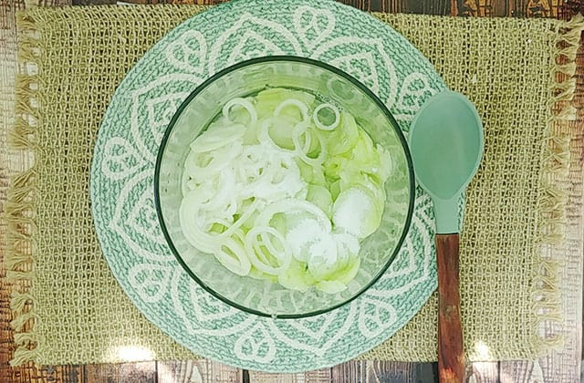 Cucumber salad recipe ingredients in a glass mixing bowl with a spoon next to it