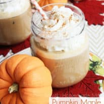 Mason jars filled with pumpkin iced coffee next to small pumpkins