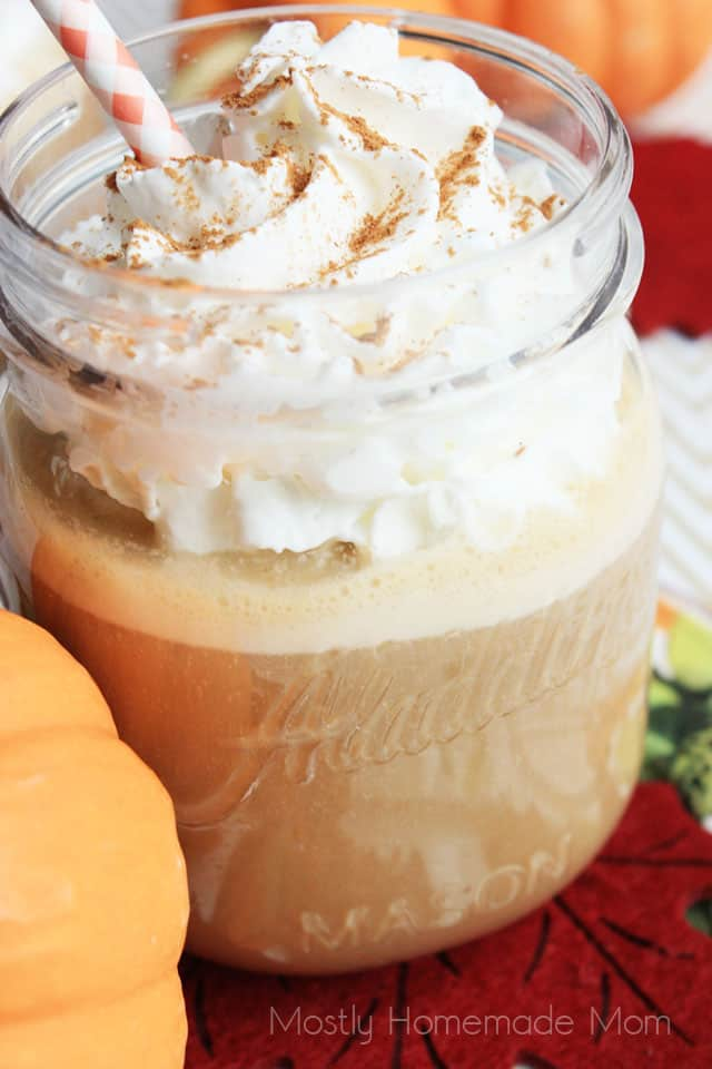 A close up picture of pumpkin iced coffee in a jar glass with whipped cream and a straw