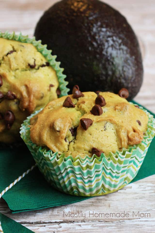 Two avocado muffins sitting on a green napkin with an avocado in the background