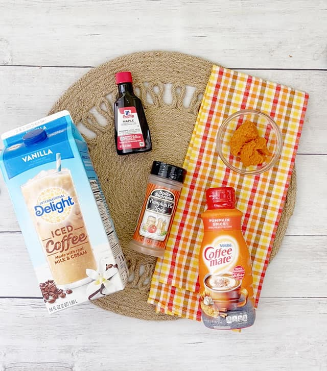 Ingredients for pumpkin iced coffee on a plaid napkin