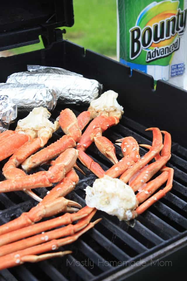 Frozen crab legs and foil wrapped corn cooking on a gas grill
