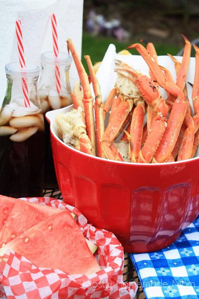 Grilled crab legs in a red bowl with sodas and watermelon