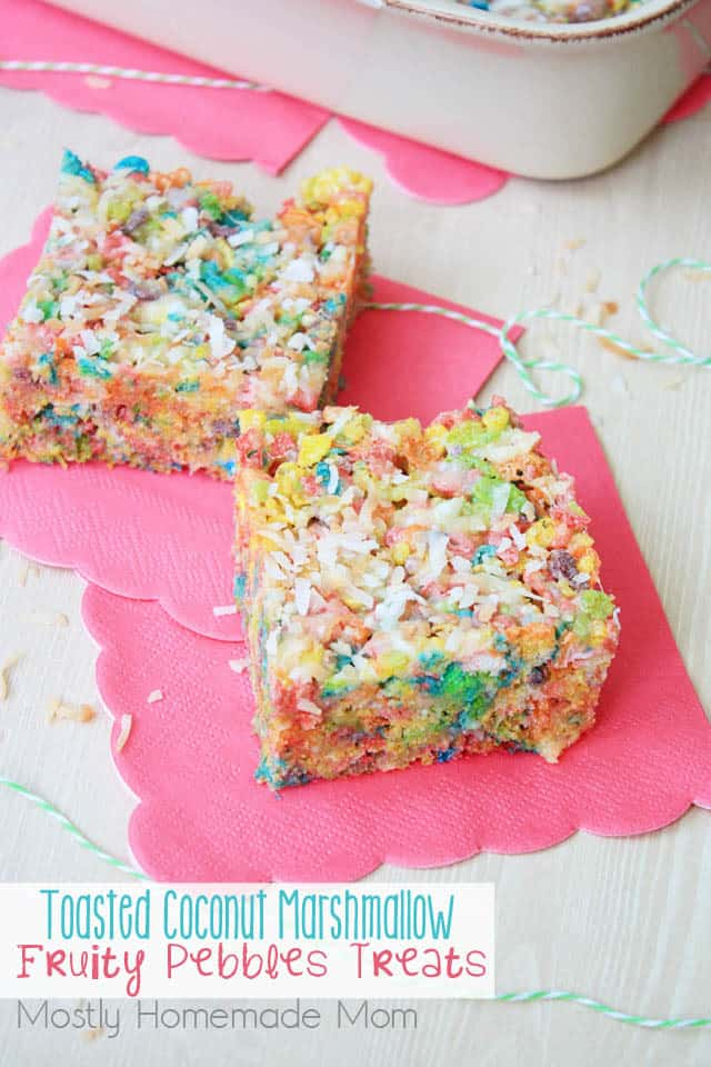 Two fruity pebbles treats on a pink napkin with coconut