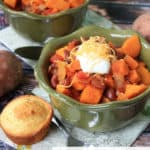 Two bowls of sweet potato chili with cornbread muffins next to them