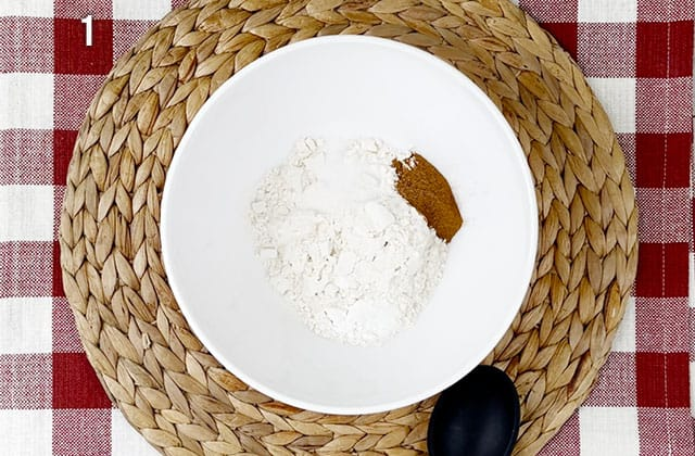 Mixing dry cake ingredients in a white bowl