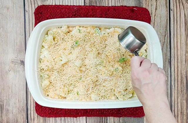 Adding Parmesan cheese to the top of a cauliflower casserole