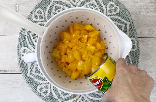 Draining peaches into a colander over a white bowl