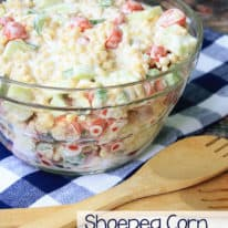 Shoepeg corn salad in a clear glass bowl with a wooden spoon