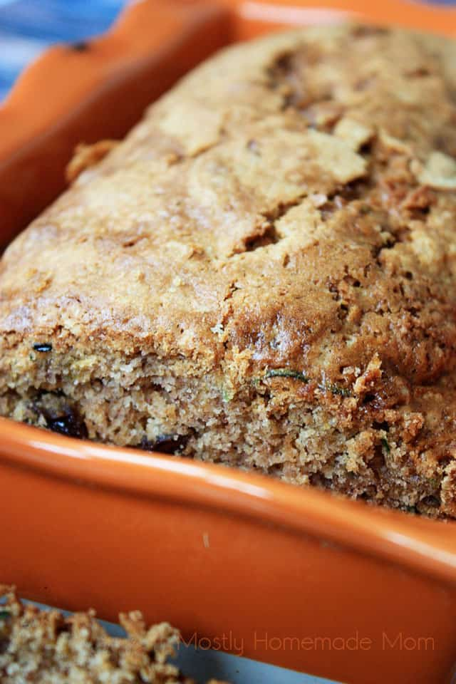Baked zucchini bread in a dish with a slice cut out of the loaf
