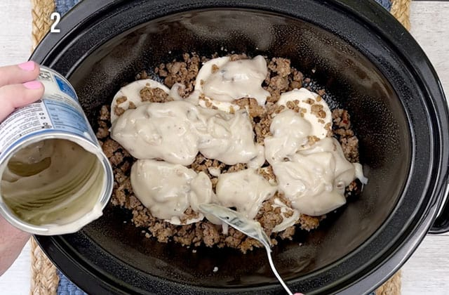 Spreading cream of mushroom soup over the sausage in a Crockpot