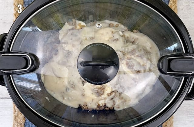 Slow cooker biscuits and gravy in a black slow cooker with the lid on