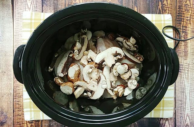 Rice, chicken breasts, and sliced mushrooms in a black crockpot