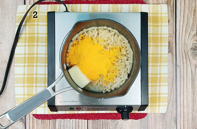 Cooking boxed macaroni and cheese in a small pan on a skillet