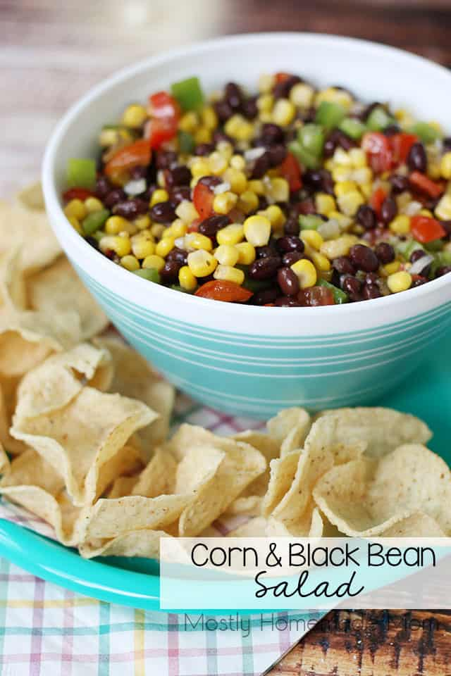 Corn and black bean salad in a bowl next to tortilla chips