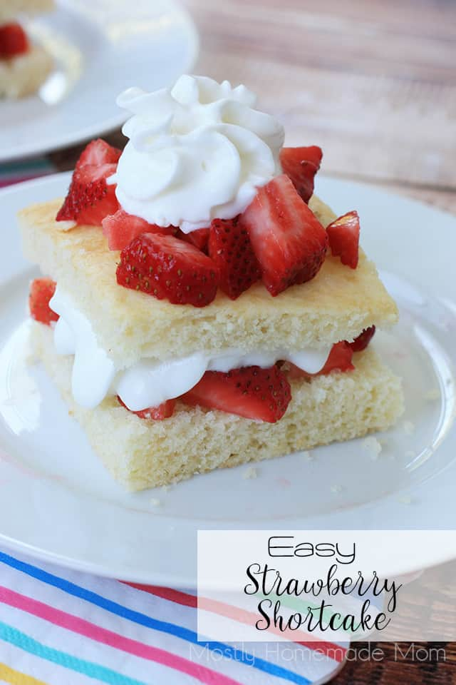 Strawberry shortcake on a plate topped with chopped strawberries and whipped cream