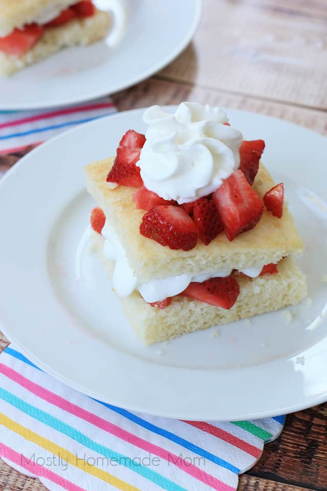 close up of finished strawberry shortcake on a white plate with a napkin