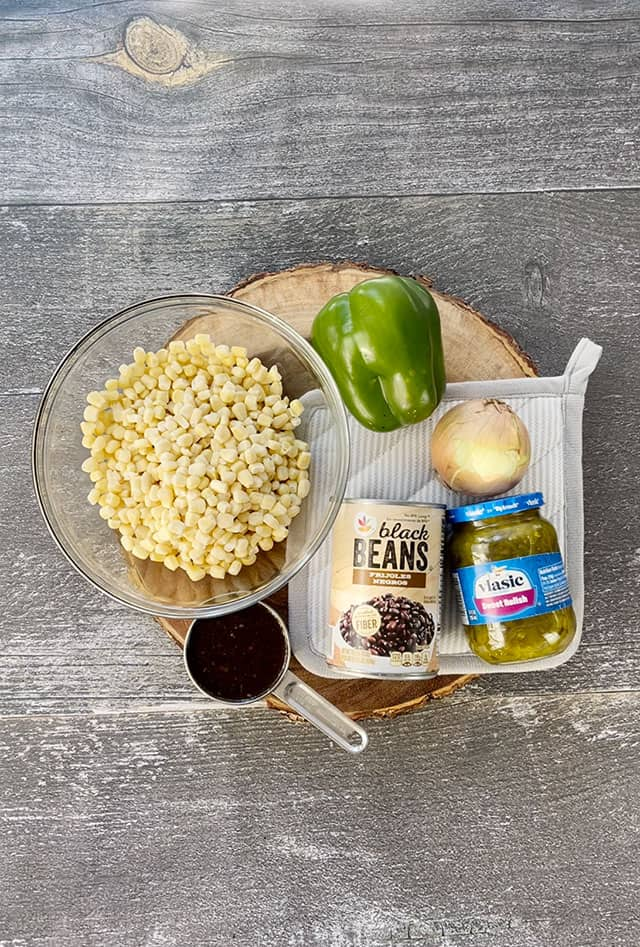 Ingredients for corn and black bean salad on a wooden stand