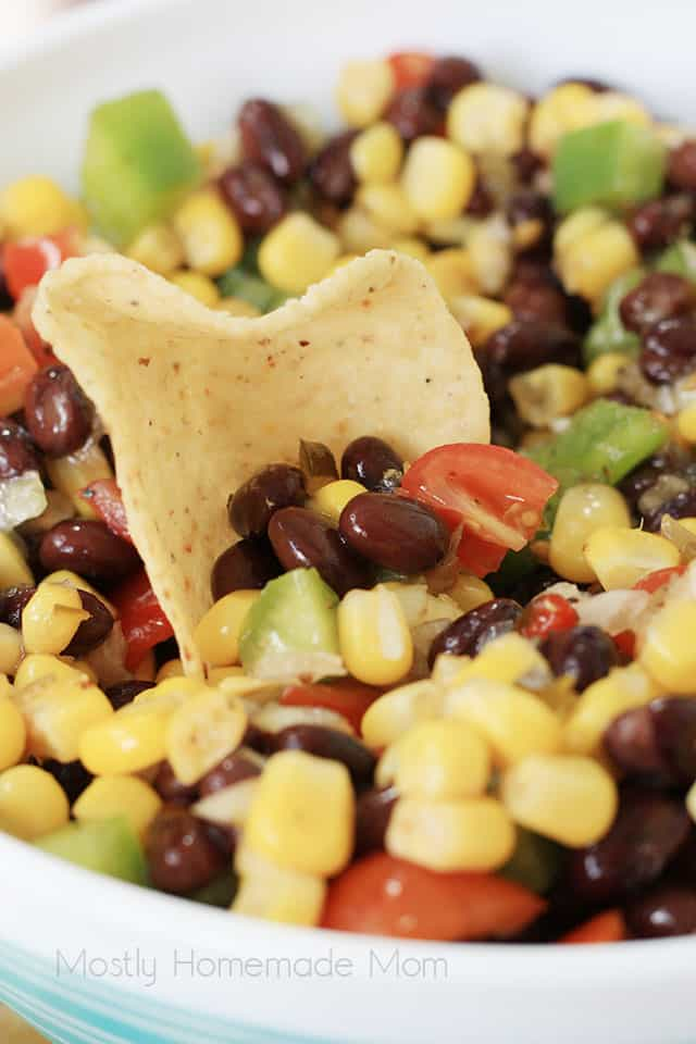 A tortilla chip taking a scoop of corn and black bean salad