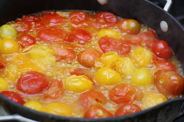 Cherry tomatoes simmering in a deep skillet
