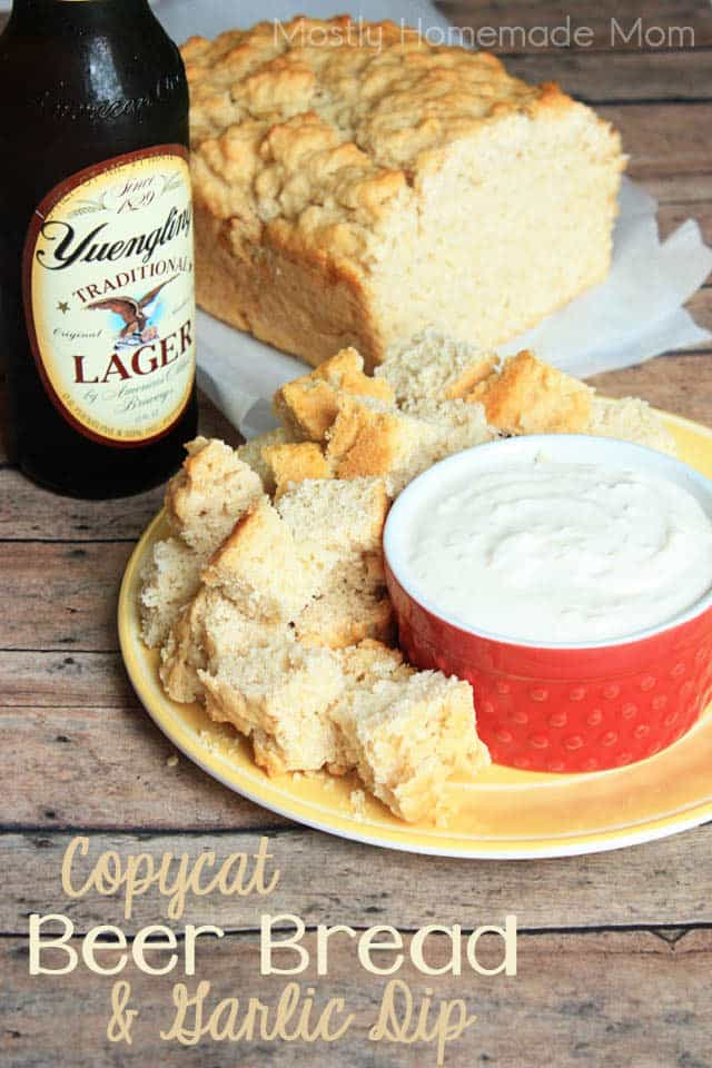 Beer bread cup up next to a garlic dip with a bottle of beer in the background