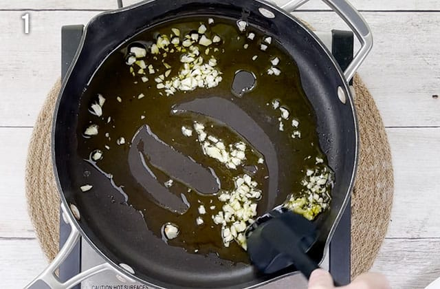 Cooking minced garlic in olive oil in a skillet
