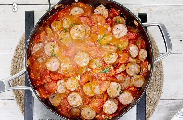 Cooking chicken sausage in a tomato sauce in a skillet