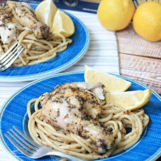 Two plates of greek lemon chicken with lemon slices over pasta