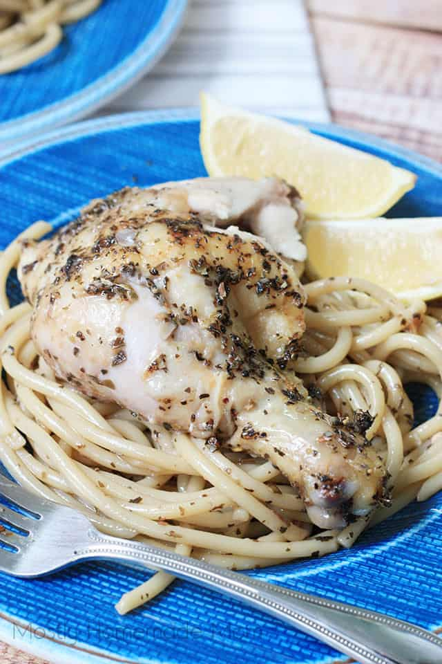 One plate of greek lemon chicken over pasta with a lemon wedge