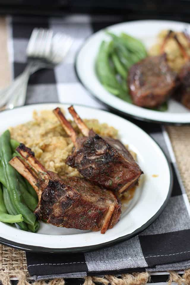 Two plates of baked lamb chops with green beans and stuffing