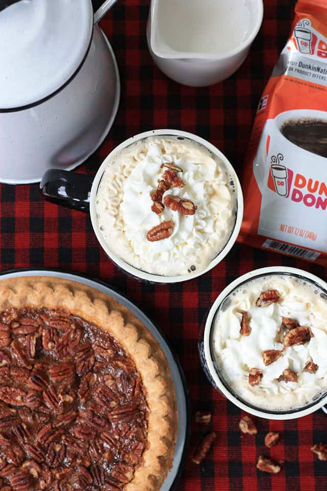 Pecan pie coffee in two mugs with a whole pecan pie being served